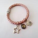 Star - € 7,95<span>VERKOCHT</span><br>Armband van gevlochten leer met zilverkleurige bedels en magneetslot - 17 cm
