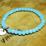 Sis & Suzy armband 011 - € 6,50<span>VERKOCHT</span><br>Smalle armband met lichtblauwe facetkralen en twee zilverkleurige bedeltjes.