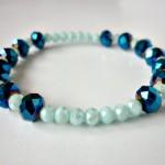 """Blue Glow - € 8,95<a href=""""/product/blue-glow"""" target=""""_blank"""">BESTELLEN</a><br>Armband met Tsjechische facetkralen in twee blauwtinten en elastisch koord - 16 cm"""
