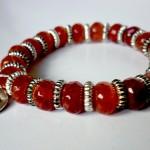 Ruby - € 12,95<span>VERKOCHT</span><br>Armband met oranjerode natuursteen, zilverkleurige fournituren en bedel, elastisch koord - 16 cm